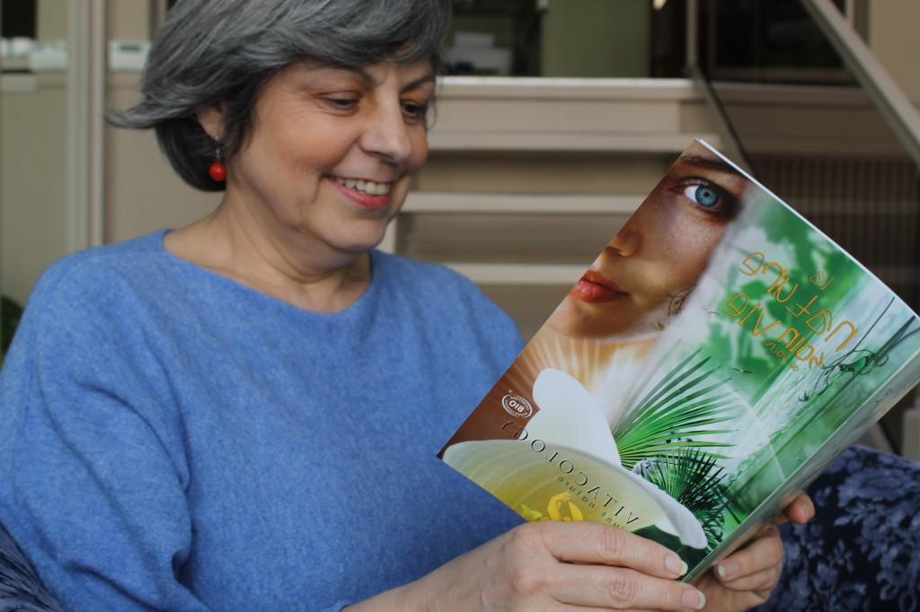 Institut Perle de Soie, une cliente sourit en regardant le catalogue de produits